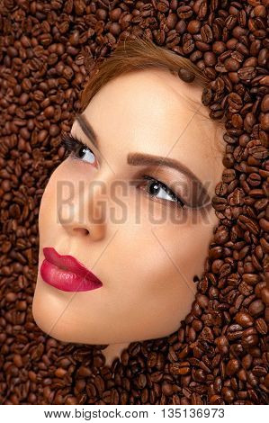 beautiful woman face in coffee beans closeup