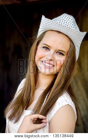 A high school senior portrait of a cowgirl in a white hat. She is holding the end of her long sandy blond hair.