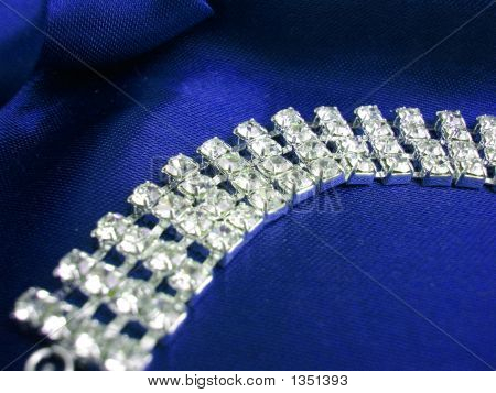 Close Up Of Dimond Necklace On A Blue Background