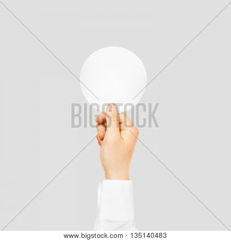 Hand holding round blank white sticker mock up isolated on gray. Sticker mockup holder. Empty paper clue remnder hold in hands.