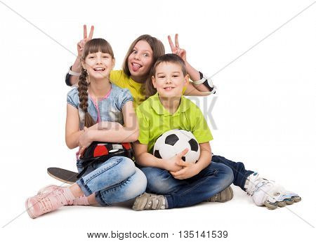 playful little boy and girls sitting on the floor with ball, skate and rollers isolated on white background