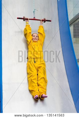 happy little girl hanging on trampoline in yellow uniform in entertainment center