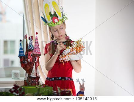 Little girl demonstrating her art craft works, Paper masher fairy castle and Easter bonnet she made. Educational and creative concept.