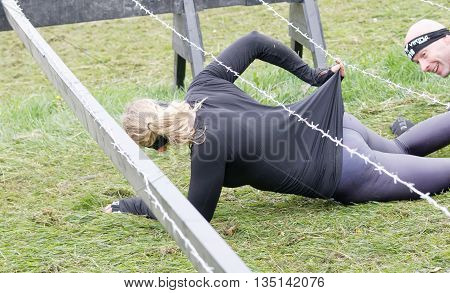 STOCKHOLM SWEDEN - MAY 14 2016: Woman get stuck in the barb wire obstacle in the obstacle race Tough Viking Event in Sweden May 14 2016