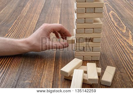 Close-up hands of man playing with wooden bricks. Entertainment activity. Education and development. Full concentration. Game of physical and mental skill. Removing blocks from a tower.