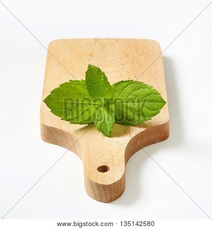 lemon balm leaves on wooden cutting board