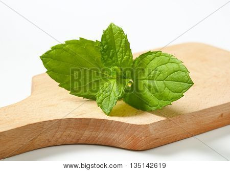 close up of lemon balm leaves on wooden cutting board