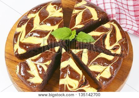 sliced chocolate cake with cream cheese on round wooden cutting board - close up