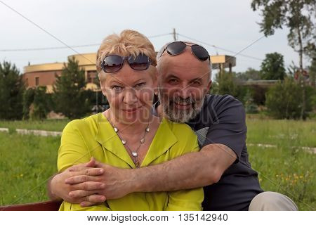 Portrait couples mature age. Sit on a park bench smiling. Man embraces a woman