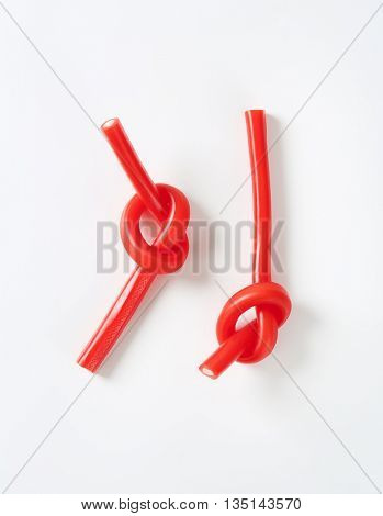 knotted strawberry candy sticks on white background