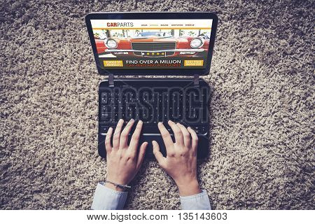 Car parts search. Auto repair shop website in a laptop computer. Top view of hands navigating in the internet.