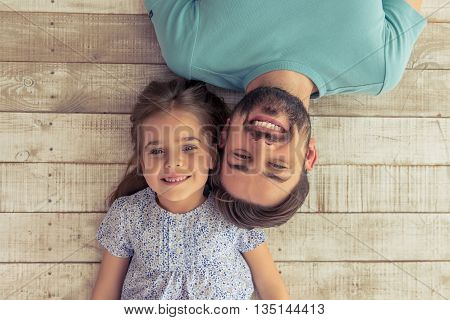 Top view of handsome young father and his cute little daughter looking at camera and smiling lying on wooden floor
