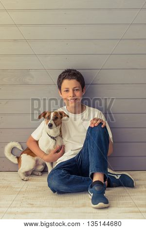 Handsome teenage boy is looking at camera and smiling while sitting with his dog on the floor