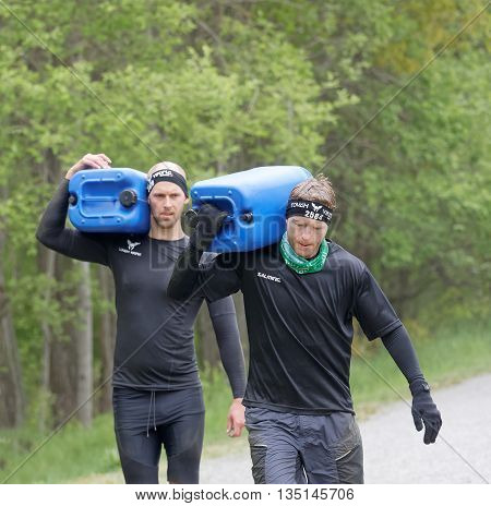 STOCKHOLM SWEDEN - MAY 14 2016: Two men carry a heavy water can in the forest in the forest in the obstacle race Tough Viking Event in Sweden May 14 2016