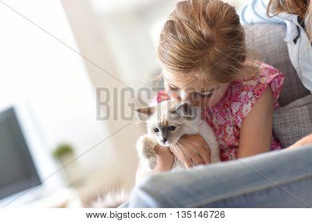 Closeup of little girl cuddling kitten