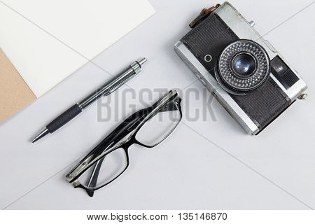 notebook with pen glasses and camera on desk with white fabric background