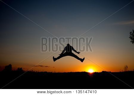 The silhouette of the man jumping with sunset backgroundconcept of happiness joy joyful life