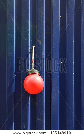 fencing of construction site with red construction light on the background of blue profiled sheet fence