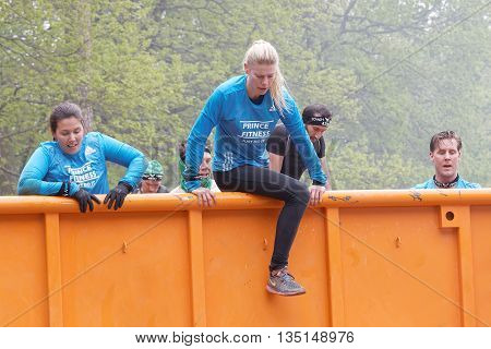 STOCKHOLM SWEDEN - MAY 14 2016: Group of woman and men climbing a orage container obstacle in the obstacle race Tough Viking Event in Sweden May 14 2016