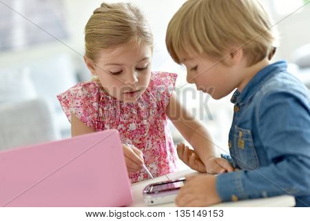 Kids playing with laptop and toy tablet