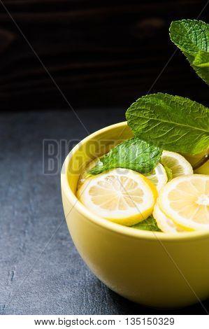 Cold lemonade. Detox cocktail. Refreshing homemade lemonade on stone table. Detox fruit infused flavored water. Refreshing summer drink