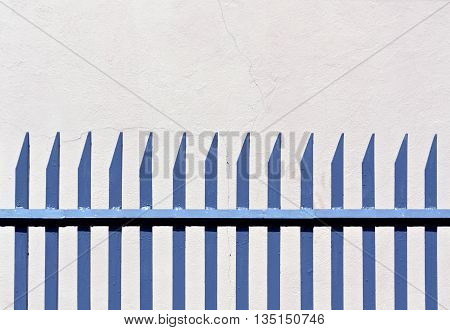 Blue Metal Fence And Plaster Wall.