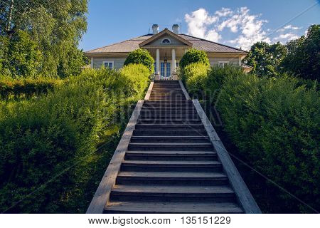 wooden staircase with a lift at the sides grow large green bushes and at the end of which stands the house of the Tree in summer day.