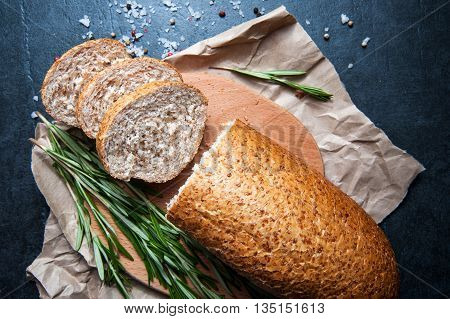 A loaf of bread with rosemary salt and pepper on paper closeup