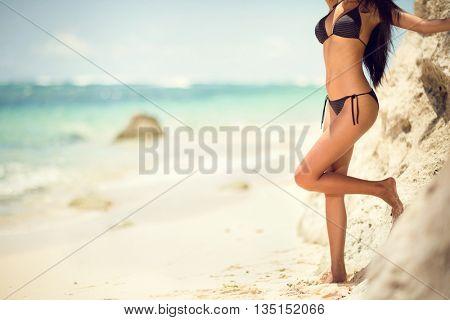 Tanned woman body in bikini on sea background