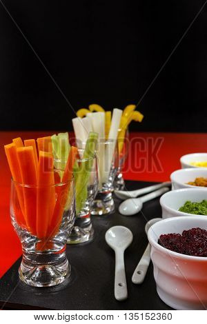 Healthy snacks - colorful vegetable sticks and mousses on red and black background