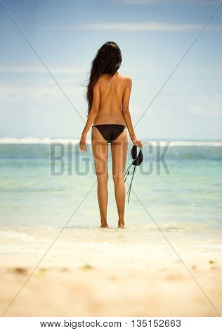 Back view of woman in topless, standing on beach