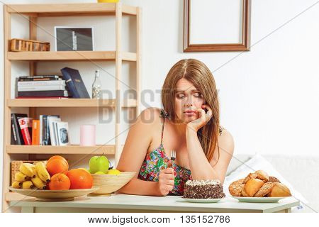 Portrait of sad fat woman sitting at table and looking at cake whether to eat it or not. Beautiful red haired lady at home.