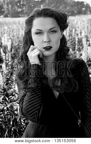 Black and white portrait of retro styled woman with vintage makeup long wavy hair taken outdoor in summer.