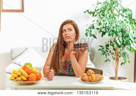 Portrait of beautiful fat woman on diet sitting at table at home and looking away. Pretty lady thinking whether to eat it or not.