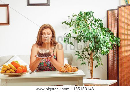 Diet concept. Beautiful fat woman on diet sitting at table full of healthy and unhealthy dishes at home.