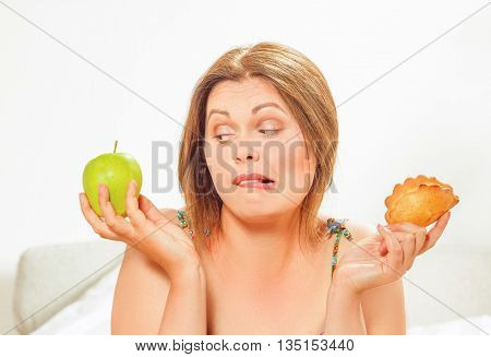 Closeup portrait of fat woman on diet looking at apple while holding cookie at home. Beautiful woman on way to be slim and slender.