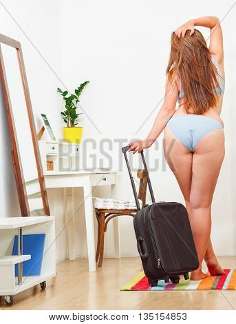 Back view of overweight woman posing with luggage or suitcase at home. Beautiful woman in underwear or lingerie with red hair.
