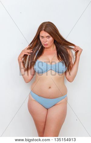 Portrait of overweight woman in underwear or lingerie posing in studio. Red haired lady on diet looking sad and disappointed.