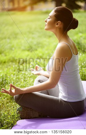 Relaxed young girl is meditating in the nature. She is sitting on mat in lotus position. Her eyes are closed with enjoyment