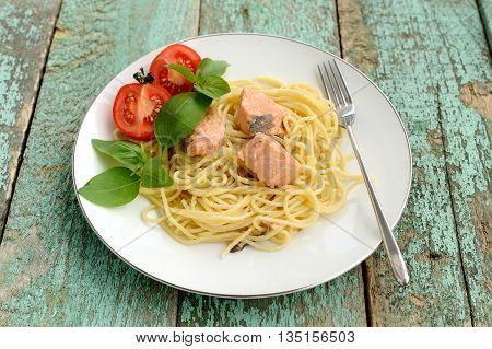 Pasta with tomatoes green basil and salmon filet in white plate horizontal