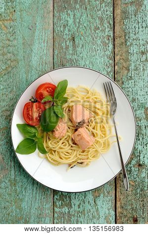 Pasta with tomatoes green basil and salmon filet in white plate on turquoise background vertical