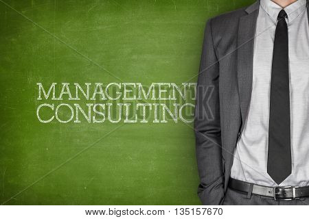 Management consulting on blackboard with businessman in a suit on side