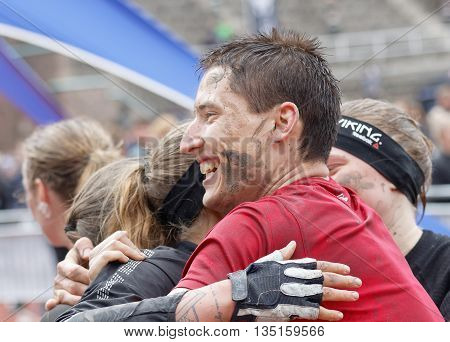 STOCKHOLM SWEDEN - MAY 14 2016: Smiling man with mud in his face hugging a woman after finishing a race in the obstacle race Tough Viking Event in Sweden May 14 2016