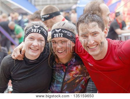 STOCKHOLM SWEDEN - MAY 14 2016: Two smiling woman and a man with mud in the face after finishing a race in the obstacle race Tough Viking Event in Sweden May 14 2016