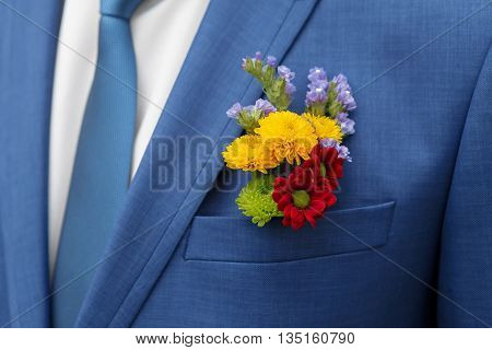 blue suit and a handsome groom's boutonniere of colorful wildflowers