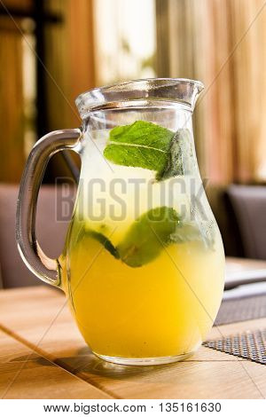 A refreshing drink in a jar on the table. Chilled juice with ice and mint