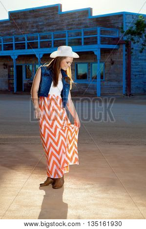 A beautiful teenage cowgirl looks down with a smile as she adjusts her long skirt. She is wearing a western hat denim jacket long skirt and boots.