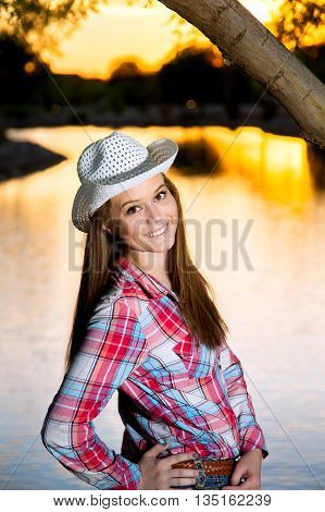 A teenage cowgirl looks over her shoulder and smiles at the camera in front of a lake at sunset.