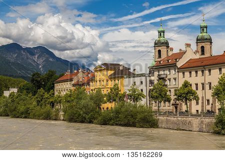 The outside of Innsbruck Cathedral during the day from across the River Inn.