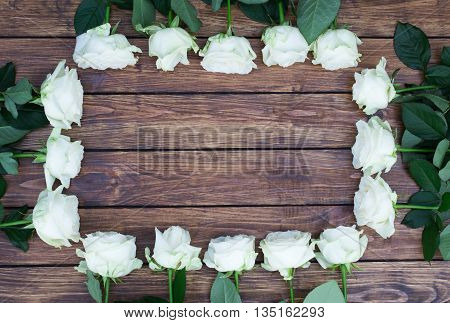 square frame of roses with green leaves on a background of brown wooden planks with a place for an inscription